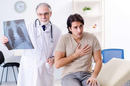 Jeune homme visitant le vieux radiologue de docteur masculin