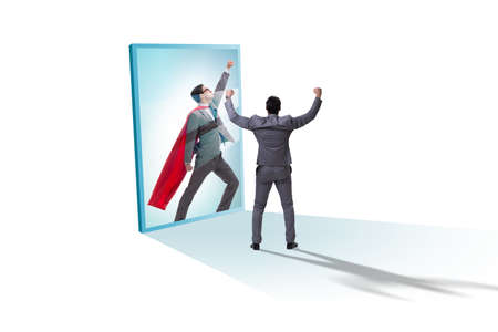 Businessman seeing himself in mirror as superhero Foto de archivo
