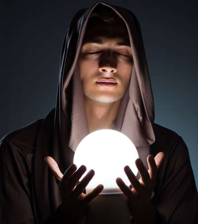 Young wizard with crystal ball in dark room Stock Photo