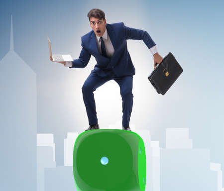 Businessman balancing on top of dice stack in uncertainty concep 免版税图像