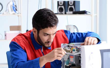 Junger Mechaniker repariert und repariert Mikrowellenherd Standard-Bild