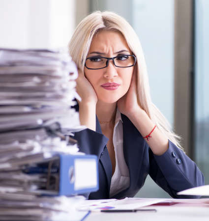 Busy businesswoman working in office at desk Imagens