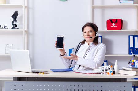 Middle-aged female doctor in telemedicine concept Stock Photo