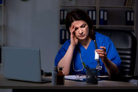 Aged female doctor working at night shift