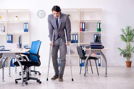 Leg injured male employee working in the office Stockfoto
