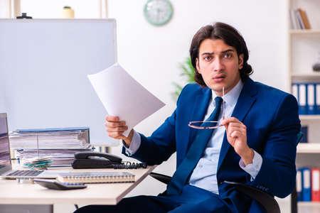 Junger Geschäftsmann, der im Büro sitzt und arbeitet Standard-Bild