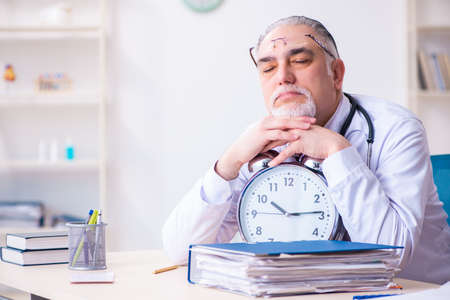 Old male doctor working in the clinic Banco de Imagens