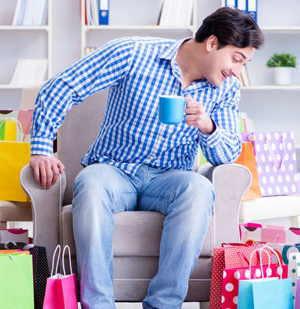 Young man after excessive shopping at home Imagens