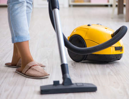 Woman doing cleaning at home with vacuum cleaner