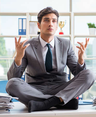 Businessman sitting on top of desk in office