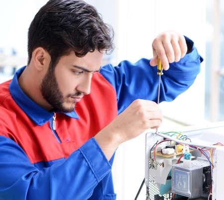 Young repairman fixing and repairing microwave oven Imagens