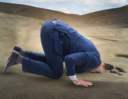 Businessman hiding his head in sand escaping from problems Фото со стока