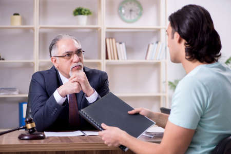 Young man visiting experienced male lawyer Stockfoto