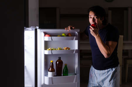 Man breaking diet at night near fridge 免版税图像