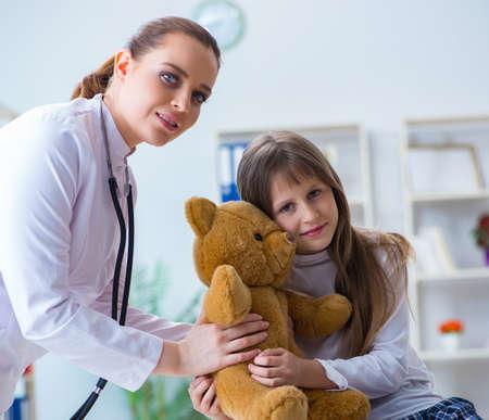 Woman female doctor examining little cute girl with toy bear Foto de archivo