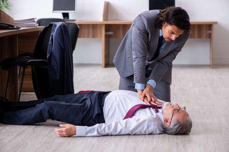 Männlicher Mitarbeiter mit Herzinfarkt im Büro