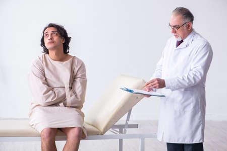 Anciano médico psiquiatra examinar paciente joven