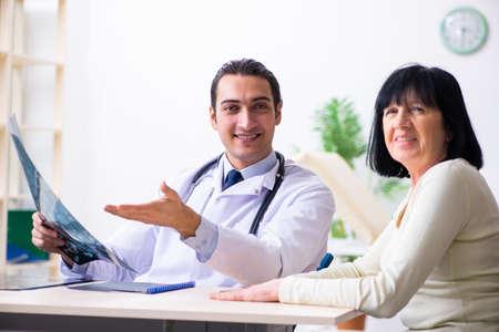 Jonge dokter die senior oude vrouw onderzoekt Stockfoto
