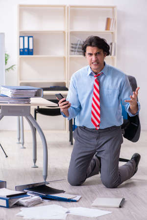 Young male employee unhappy with excessive work Stock Photo