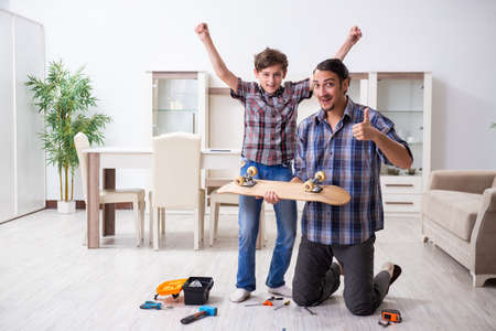 Young father repairing skateboard with his son at home