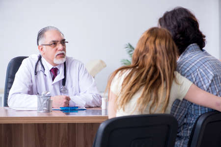 Young couple visiting old male doctor Imagens