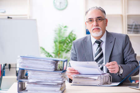 Aged male employee unhappy with excessive work Imagens