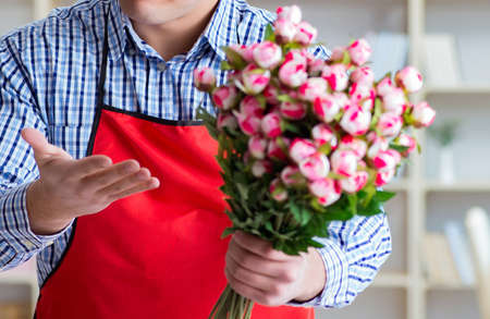 Flower shop assistant offering a bunch of flowers 스톡 콘텐츠