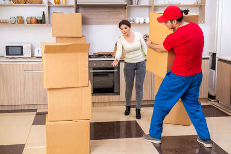 Young male contractor and female customer in moving concept Stockfoto