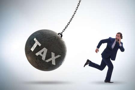 Businessman running away from high taxes Foto de archivo