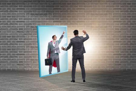 Businessman seeing himself in mirror as superhero Banque d'images