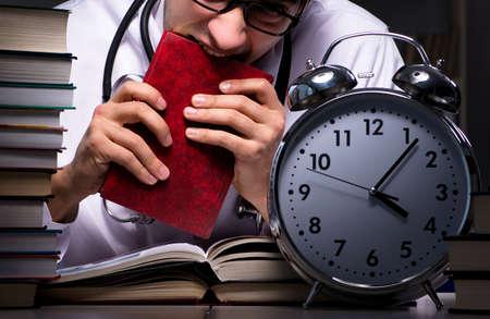 Medical student preparing for university exams at night Stockfoto