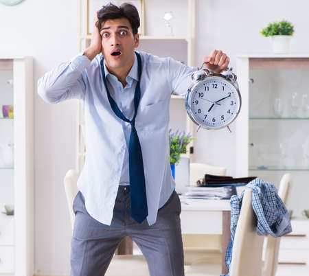 Businessman late for office due to oversleeping after overnight Stockfoto - 128319401