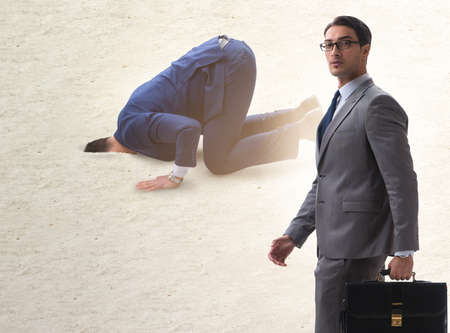Businessman hiding his head in sand escaping from problems Stockfoto