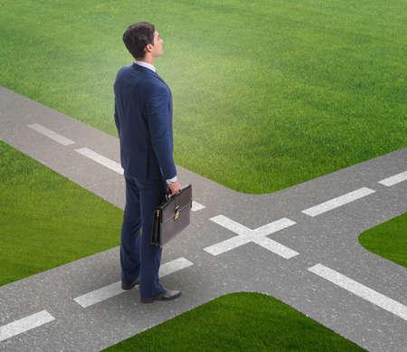 Junger Geschäftsmann an der Kreuzung im Ungewissheitskonzept
