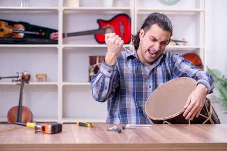 Young handsome repairman repairing drum