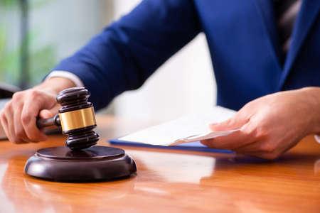 Młody sędzia płci męskiej siedzący na sali sądowej