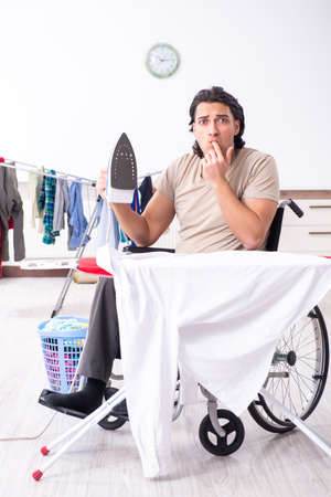 Young man in wheel-chair doing ironing at home