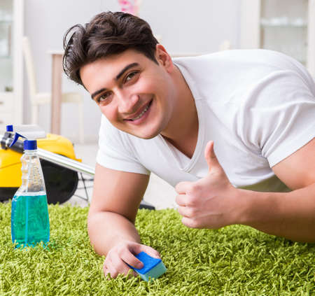 Young husband man cleaning floor at home Stockfoto