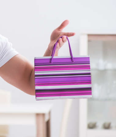 Young man with gift bag at home preparing suprise for wife Imagens