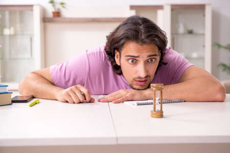 Young male student preparing for exams at home Banco de Imagens