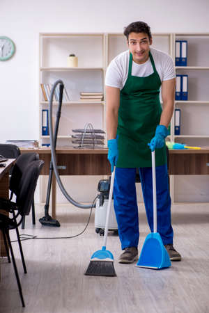 Young handsome contractor cleaning the office Stockfoto