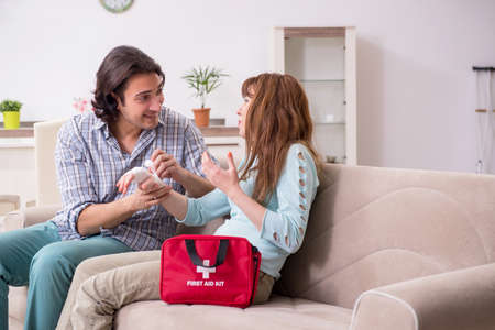 Young couple in first aid concept at home