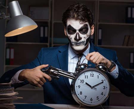 Empresario con mascarilla aterradora trabajando hasta tarde en la oficina Foto de archivo