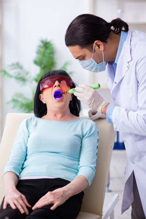 Old woman visiting young doctor dentist Stock Photo