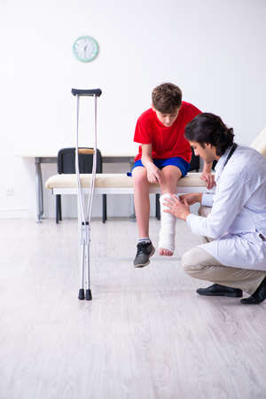 Leg injured boy visiting young doctor traumatologist