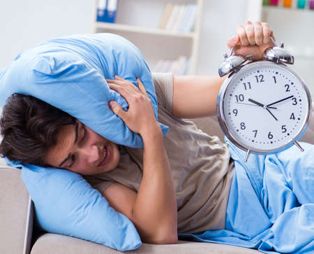 Man having trouble waking up with alarm clock Stockfoto - 128707673