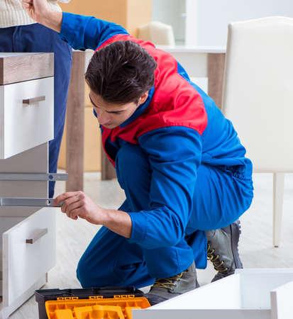 Der Auftragnehmer-Mechaniker, der Möbel unter der Aufsicht einer Frau zusammenbaut