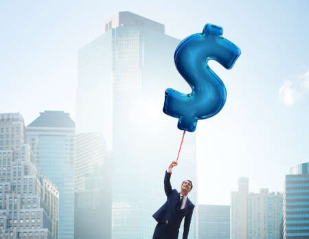 Businessman flying on dollar sign inflatable balloon