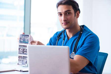 Junger männlicher Arzt, der Doppler-Bilder betrachtet Standard-Bild