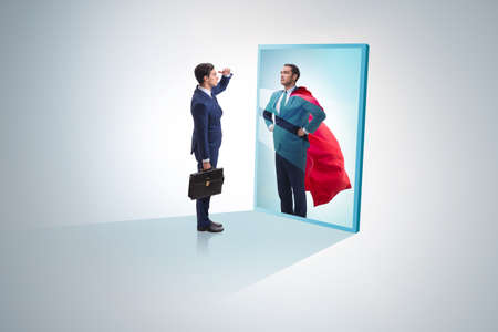 Businessman seeing himself in mirror as superhero 스톡 콘텐츠